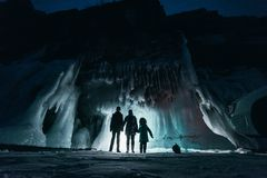Surreal landscape with people exploring mysterious ice grotto cave. Outdoor adventure. Family exploring huge icy cave. Dark majestic landscape. Magical stock photo