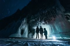 Surreal landscape with people exploring mysterious ice grotto cave. Outdoor adventure. Family exploring huge icy cave. Dark majestic landscape. Magical royalty free stock images