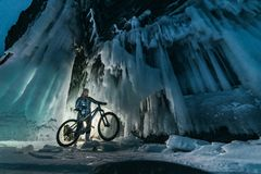 Surreal landscape with woman exploring mysterious ice grotto cave. Outdoor adventure bike. Girl exploring huge icy cave. Dark majestic landscape. Magical stock images