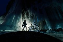 Surreal landscape with woman exploring mysterious ice grotto cave. Outdoor adventure bike. Girl exploring huge icy cave. Dark majestic landscape. Magical royalty free stock photography