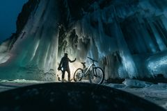 Surreal landscape with woman exploring mysterious ice grotto cave. Outdoor adventure bike. Girl exploring huge icy cave. Dark majestic landscape. Magical royalty free stock image