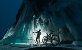 Surreal landscape with woman exploring mysterious ice grotto cave. Outdoor adventure bike. Girl exploring huge icy cave. Dark majestic landscape. Magical stock photos