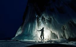 Surreal landscape with woman exploring mysterious ice grotto cave. Outdoor adventure. Girl exploring huge icy cave, dark. Majestic landscape. Magical royalty free stock photography