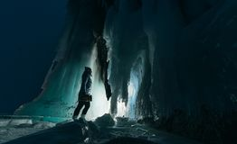 Surreal landscape with woman exploring mysterious ice grotto cave. Outdoor adventure. Girl exploring huge icy cave, dark. Majestic landscape. Magical royalty free stock photos