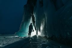 Surreal landscape with woman exploring mysterious ice grotto cave. Outdoor adventure. Girl exploring huge icy cave, dark stock photography