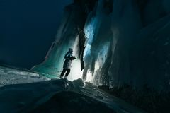 Surreal landscape with woman exploring mysterious ice grotto cave. Outdoor adventure. Girl exploring huge icy cave, dark. Majestic landscape. Magical stock images