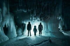 Surreal landschap met mensen die het geheimzinnige hol van de ijsgrot onderzoeken Openlucht Avontuur Familie die reusachtig ijzig royalty-vrije stock fotografie