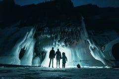 Surreal landschap met mensen die het geheimzinnige hol van de ijsgrot onderzoeken Openlucht Avontuur Familie die reusachtig ijzig stock foto's