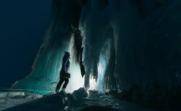 Surreal landschap met vrouw die het geheimzinnige hol van de ijsgrot onderzoeken Openlucht Avontuur Meisje die reusachtig ijzig d royalty-vrije stock foto's