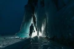 Surreal landschap met vrouw die het geheimzinnige hol van de ijsgrot onderzoeken Openlucht Avontuur Meisje die reusachtig ijzig d stock fotografie