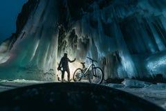 Surreal landschap met vrouw die het geheimzinnige hol van de ijsgrot onderzoeken Openluchtavonturenfiets Meisje die reusachtig ij royalty-vrije stock afbeelding