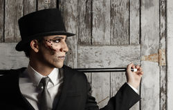 Surreal man in top hat. Fantastical stylized portrait of man in top hat and and cane in surrealistic makeup Stock Photography
