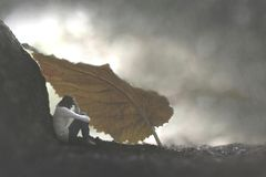 Surreal moment of a small woman who protects herself from the rain by sheltering herself under a leaf stock photography