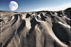 Surreal Moonscape. From combined photographs of sandy beach and full moon Royalty Free Stock Photography