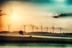 Surreal morning sunrise on the fields with wind turbines in the background Royalty Free Stock Images