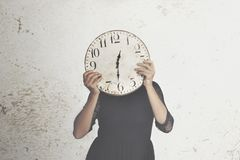 Surreal photo of a woman hiding behind a big clock stock photography