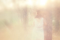 Surreal photo of young woman standing in forest. image is textured and toned. dreamy concept. Stock Photo