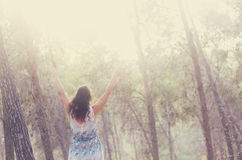 Surreal photo of young woman standing in forest. image is textured and toned. dreamy concept Stock Photography