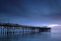 Surreal pier. Old wooden pier with surrounded by blue water and blue clouds. There are some people walking and fishing Royalty Free Stock Photos