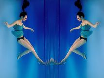 Portrait of beautiful slim stylish brunette in blue dress and heels shoes underwater. Surreal portrait with reflection of beautiful slim stylish brunette in blue stock image