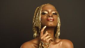 Surreal Portrait of African American Woman with Glossy Golden Makeup and Headwear. Bronze Bodypaint.  stock video