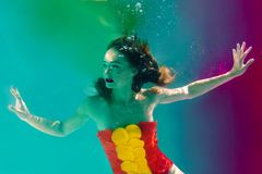 Surreal portrait of young attractive woman with air bubbles underwater in colorful water with ink. In the swimming pool Stock Image