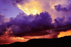 Surreal purple and red storm clouds around orange sun rays. Dramatic dark purple and red storm clouds billow around a bright gap through which light rays stream Royalty Free Stock Images