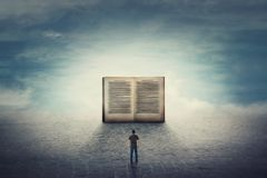 Surreal scene as student guy stands on a pavement road in front of a giant opened book. The importance of reading and literature. In the modern world. Education royalty free stock photos