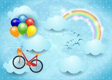 Surreal sky with clouds, rainbow and hanging bike Royalty Free Stock Images
