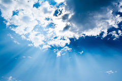 Surreal sun rays are striking through the clouds like an explosi Royalty Free Stock Image