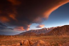 Surreal sunset. Huge lenticular cloud painted by the setting sun over the Sierra Nevada mountain range with Alabama Hills in the foreground, California Stock Photo