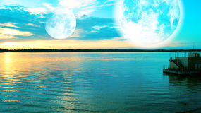 Surreal sunset over river with  two Moons Royalty Free Stock Photo