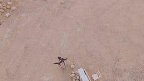 Surreal verhaalmeisje dichtbij de witte piano in de woestijn tegen de achtergrond van bergen Lucht Mening Mening van stock video