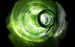 Surreal Vibrant Glass Bottle. Surreal vibrant green glass bottle backlit by bright light, casting a glowing hue across a dark sci fi like rugged tunnel stock photos