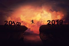Between 2018 and 2019. Surreal view as a businessman jump over a chasm obstacle between 2018 and 2019 years. Self overcome new year concept, way to win and royalty free stock images