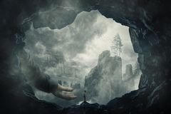 A. Surreal view as a wander girl silhouette on the edge of a cave stand in front of a giant stretched hand. Mystery hand of help and protection to cross the Stock Photos