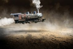 Surreal Vintage Train Locomotive, Flying. Surreal retro vintage steam train locomotive. The steam engine is flying through the sky above a desolate desert royalty free stock photos
