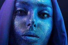 Surreal vrouw in blauwe bodyart met schittert stock foto's