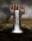 Surreal Waterfall, Desolate Desert Landscape. Surreal scene of a human hand and waterfall in a desolate desert. The surrealism includes a tornado storm and Royalty Free Stock Image