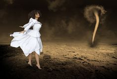 Surreal Woman, Fantasy, Tornado, Storm. Abstract concept of a beautiful woman wearing a white dress is standing in a desolate desert with a tornado storm. The Stock Photography