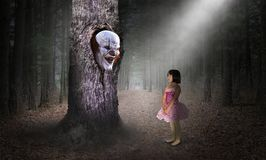 Surreal Child, Clown, Evil, Imagination, Danger. Surreal young girl child and an evil clown in a hollow tree. The nightmare scene of horror gives imagination for Stock Photography