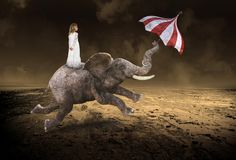 Surreal Young Girl, Flying Elephant, Desolate Desert. Surreal young girl is riding a flying elephant in a desolate desert. The wildlife animal uses an umbrella Stock Photos
