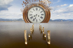 Surreale gebrochene Uhr im Meer stockbilder