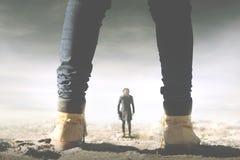 Surreale Sitzung zwischen einem Riesen und einer kleinen Frau lizenzfreie stockfotografie