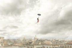 Surrealer Moment eines Frauenfliegens mit ihrem Regenschirm über der Stadt lizenzfreie stockbilder