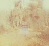 Surrealer unscharfer Hintergrund der jungen Frau steht im Waldabstrakten und träumerischen Konzept das Bild ist strukturiert und  Stockfoto