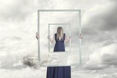 Surreales Bild einer Frau, die einen Rahmen hält, der sich reflektiert lizenzfreies stockfoto