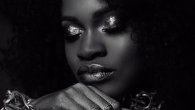 Surreales Schwarzweiss-Nahaufnahmeporträt des weiblichen Modells des jungen Afroamerikaners mit Goldglattem Make-up Gesicht Art Stockfotografie
