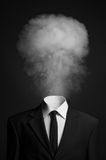 Surrealism and business topic: the smoke instead of a head man in a black suit on a dark background in the studio stock photography
