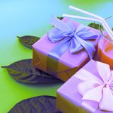 Surrealism Holiday poster Boxes with gifts a glass of milkshake a bright green background. Festive summer party Stock Photography